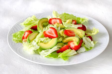 Salad with avocado, strawberries and lettuce on white background. Horizontal