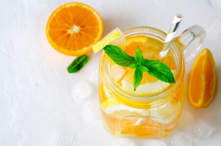 Summer refreshing iced drinks with orange, lemonand mint on white background, top view Standard-Bild