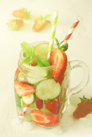 Summer refreshing iced drinks with cucumber and strawberry on white background, vertical, toned
