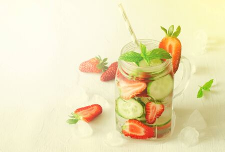 Summer refreshing iced drinks with cucumber and strawberry on white background, toned, copy space Standard-Bild