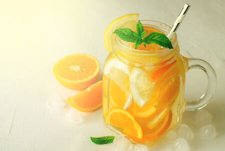 Summer refreshing iced drinks with orange, lemonand mint on white background, toned, copy space