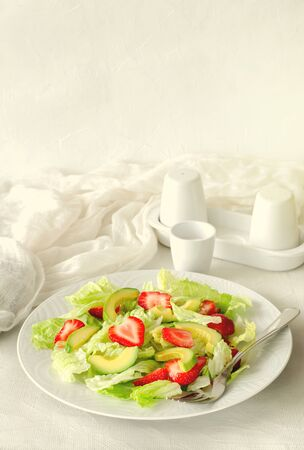 Salad with avocado, strawberries and lettuce on white background. Copy space, vertical