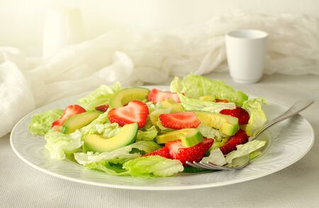 Salad with avocado, strawberries and lettuce on white background. Horizontal, toned Standard-Bild