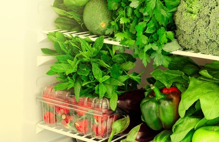 Greens, fruits and vegetables in fridge. Vegan, vegetarian healthy lifestyle concept. Horizontal, toned