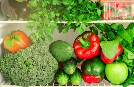 Greens, fruits and vegetables in fridge. Vegan, vegetarian, raw healthy lifestyle concept. Toned