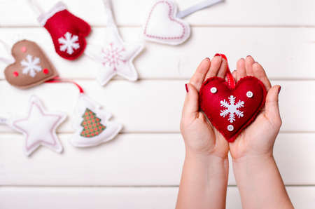 Red felted heart in femaile hand on white wooden background. Xmas and Happy New Year composition Standard-Bild