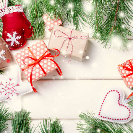 Christmas gift boxes with red ribbon on white background with Fir branches. Xmas and Happy New Year composition. Square, top view Standard-Bild