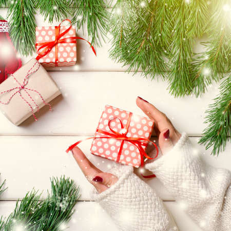 Female hands holding Christmas gift box on whitr background. Horizontal, copy space.