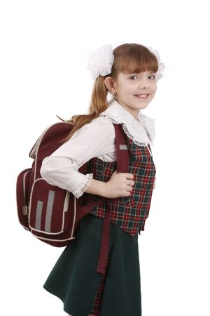 Young school girl ready for school. Little pupil is going to school. Happy young schoolgirl with satchel white background. Portrait of smiling, little girl in school uniform with backpack.  Education, learning, teaching. Stock Photo