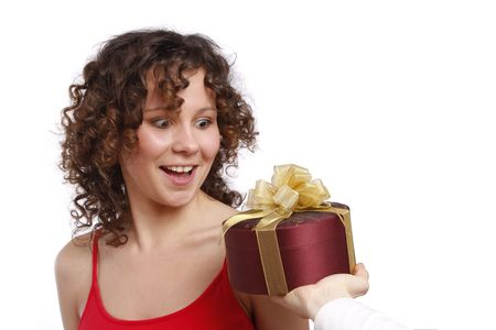 Beautiful woman with a gift. Attractive girl holding purple box with gold ribbon. Woman is surprising at present. Isolated over white background. photo