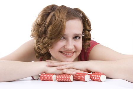 haircurlers: Nice girl with red hair-curlers. Smiley woman with hair-rollers. Young attractive housewife with curlers in hair. Isolated on white in studio.