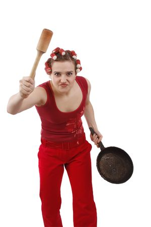 Woman in hair rollers. Housewife with curlers in her hair, holding a frying pan. Portrait of a young girl with an angry expression. Very frustrated and angry mad woman. Angry look on face. Studio, white background.