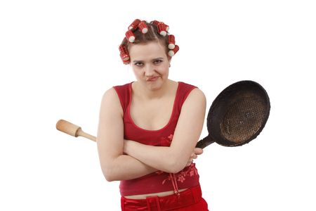 Woman in hair rollers is holding a frying pan.  Very frustrated and angry mad woman. Angry look on face. Studio, white background. Stock Photo