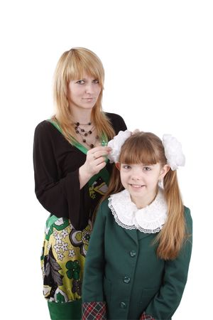 Mother is helping hers young daughter prepare to school. Woman is filleting ribbon on girls hair.  Mom is brushing young schoolgirls hair. Isolated on white in studio photo