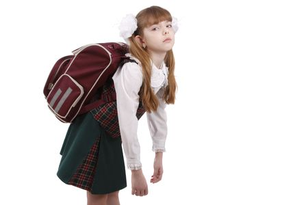 School girl is tired. Schoolgirl in school uniform with backpack. Pupils satchel is very heavy.  Sad teenager. A heavy load to bear. Isolated on white in studio. Stock Photo