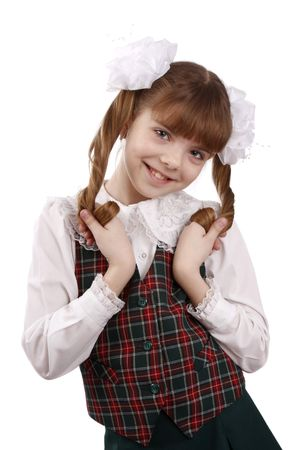 Little girl in school uniform. Pupil is trifling with hair. Isolated on white in studio. Stock Photo - 5026579