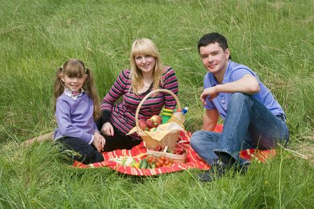 Family having picnic in park. Parents and child on picnic in the forest. Mother, father and daughter relaxing.