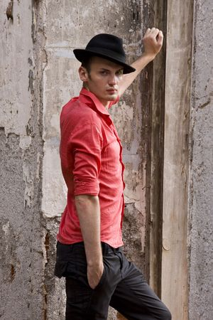 Elegant fashion man model wear red shirt and hat near bare walls. Handsome young man look. Young casual man portrait wear a hat