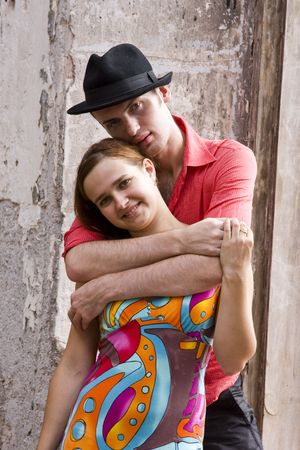 evening wear: Romantic couple is embracing. Portrait of a happy couple near bare walls.  Charming young girl and boy spending quality time.  Fashion man model wear red shirt and hat near bare walls.  Girl  wear bright colour evening dress.