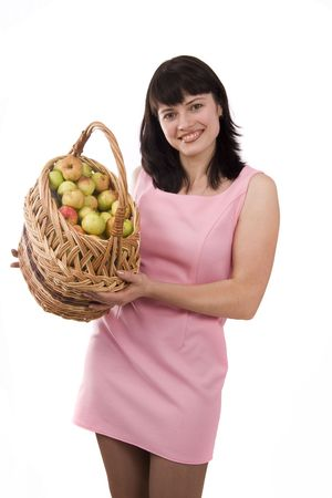 Woman in pink dress is standing and holding a basket full apples on white background. Beautiful girl holding a basket of delicious fresh fruits. Isolated over white. Stock Photo - 5405371