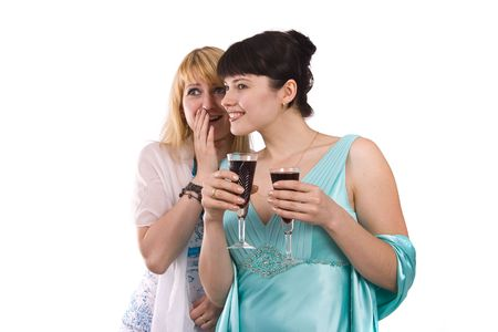 greenness: Gossip - two beautiful girls in studio shot.  Happy young women friends talking and laughing.  Girl in greenness of the sea dress is standing and holding wine glass. Woman in white dress is telling a secret to another. Isolated on white background.