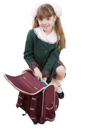 Schoolgirl is packing up schoolbagl. Isolated on white in studio.