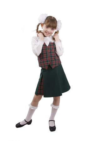 Little girl in school uniform. Pupil is trifling with hair. Isolated on white in studio.