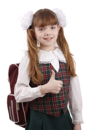 Portrait of smiling, little girl in school uniform. Young pupil is going to school. School girl showing thumbs up on white background.  School girl looking into the camera while giving an ok gesture with her forward hand. Happiness girl shows OK.  Isolate photo