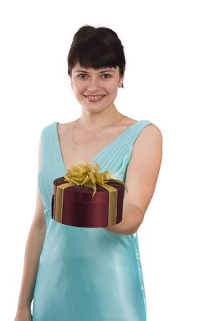 greenness: Beautiful smiling woman with a gift.  Girl in greenness of the sea dress is standing and holding purple box with gold ribbon on white background. Female is giving the gift.  Isolated over white background.