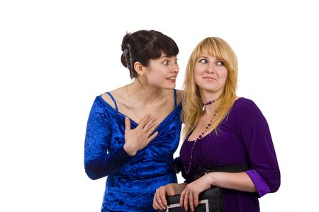 chatty: Girl telling a secret to another - gossip isolated over a white background. Woman friends series. Two happy women sharing funny gossip. Gossip - two beautiful girls in studio shot.  Happy young women friends talking and laughing.  Woman in blue dress is t Stock Photo