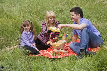 Family having picnic in park. Parents and child on picnic in the forest. Mother, father and daughter relaxing. Wife is giving husband sandwich.  photo