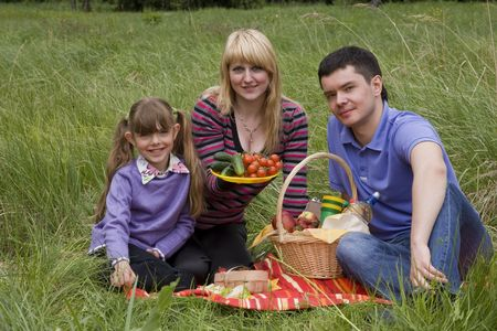 Family having picnic in park. Parents and child on picnic in the forest. Mother, father and daughter relaxing. Woman is holding vegetables. photo