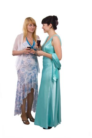 greenness: Girl telling a secret to another - gossip isolated over a white background. Woman friends series. Two happy women sharing funny gossip. Girl in greenness of the sea dress is standing and holding wine glass. Woman in white dress is telling a secret to anot