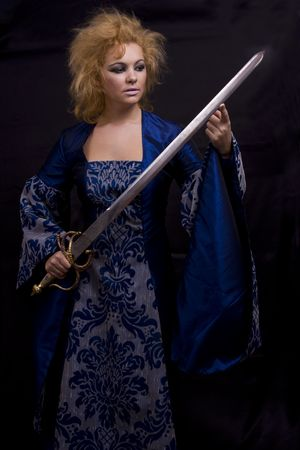 Woman in medieval  dress is holding weapon. Horrible witch with sword on black background.  photo