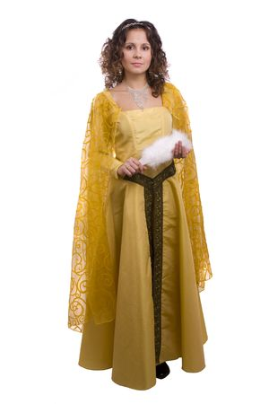 costume jewelry: Woman wearing fancy yellow dress on Halloween. A young woman dressed up as princess. Cute girl in medieval era costume on white background. Stock Photo