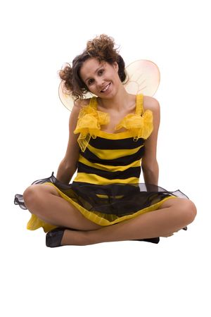Woman wearing fancy dress on Halloween is sitting on the floor. A young woman dressed up as bumblebee is smiling. Cute girl in bee costume on white. photo