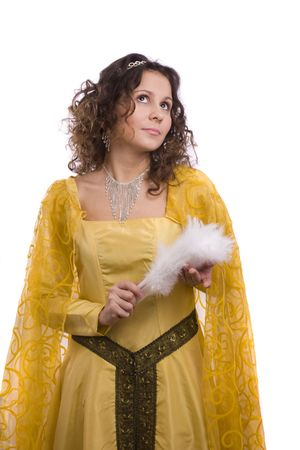 Woman wearing fancy yellow dress on Halloween. A young woman dressed up as princess. Cute girl in medieval era costume on white background. Stock Photo