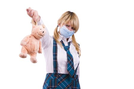 Pig flu virus.  Schoolgirl is wearing surgical mask and is afraid of pig. Young woman with respiratory mask and pig is sitting on her shoulder. Picture is symbolizing swine flu or influenza AH1N1 virus Stock Photo - 5912375