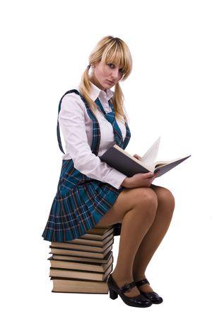 colegiala: Estudiante de secundaria de senior en uniforme con documentos est� sentado en la pila de libro. Alumna de la joven y bella es que llevaba un tradicional uniforme est� leyendo el libro de texto. Foto de archivo