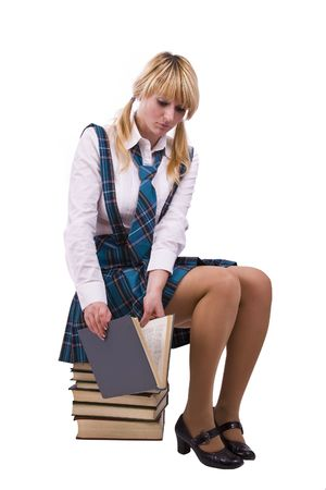 furtively: Senior high school student in uniform with documents is sitting on the stack of book. Young and beautiful schoolgirl  is wearing a traditional uniform watch furtively at the textbook.