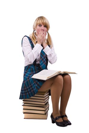 school uniform girl: Senior high school student in uniform is sitting on the stack of book and study up. Young and beautiful schoolgirl  is wearing a traditional uniform is shocked by something.