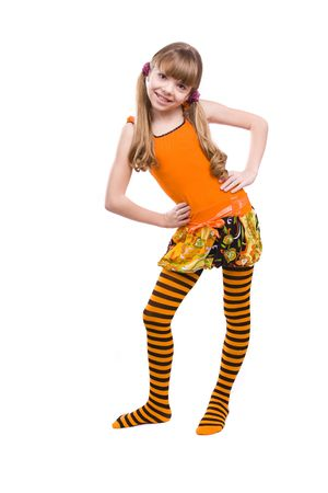 Little girl in the orange dress is standing. Portrait of an attractive young teenager is smiling in orange over white background. photo