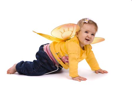 Baby is creeping on the floor. Photo of small child is wearing in yellow jersey and wings. Baby is 9 months. photo
