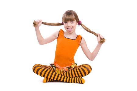 Little girl in the orange dress is putting out ones tongue and is sitting on the floor. Portrait of an attractive young teenager is smiling in orange over white background. photo