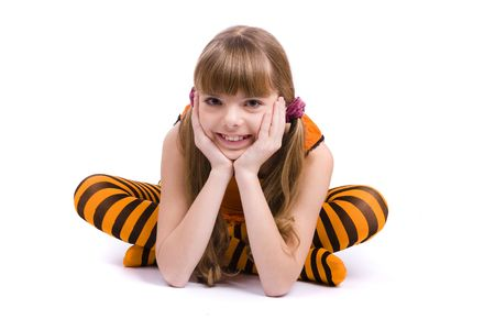 Little girl in the orange dress is sitting on the floor. Portrait of an attractive young teenager is smiling in orange over white background. photo