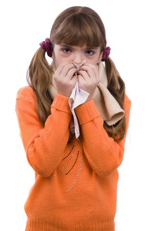 Sneezing. Little girl on white background in winter clothing is sick. Female have sore throat and sneezing. photo