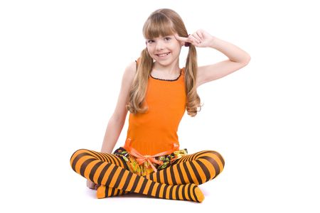Little girl in the orange dress with finger near her head is sitting on the floor. Portrait of an attractive young teenager is  playing the fool and smiling in orange over white background. photo