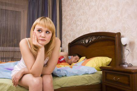 sleeplessness: Giovane coppia in un letto di donna annoiato. Donna e uomo, avendo un dissenso. Maschio � addormentato e femmina con espressioni triste.