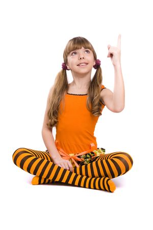 Little girl in the orange dress is sitting on the floor and pointing to up. Portrait of an attractive young teenager is smiling in orange over white background. photo