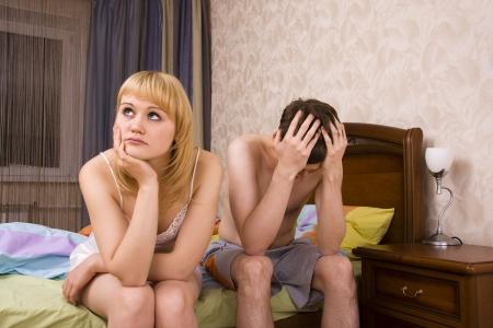 parejas sensuales: Joven pareja en una mujer aburrido de la cama. Mujer y hombre, tener un disagreement.Male y la hembra con expresiones tristes.